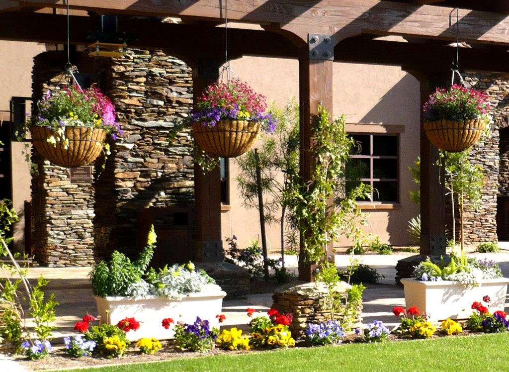 Hanging Baskets, Pots and Beds Create a Living Dividerin a Desert Potted Garden